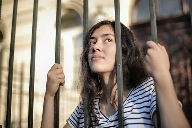 woman looking away through fence