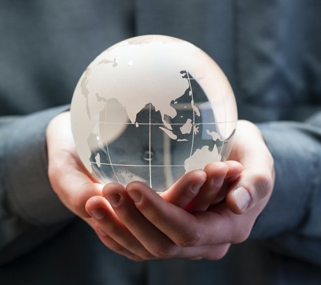 both hands holding a miniature white globe