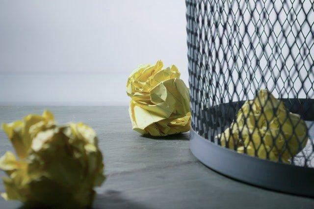 crumpled paper outside the trash bin