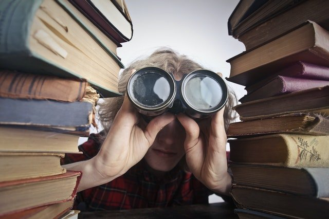 person with binoculars looking through stacked books