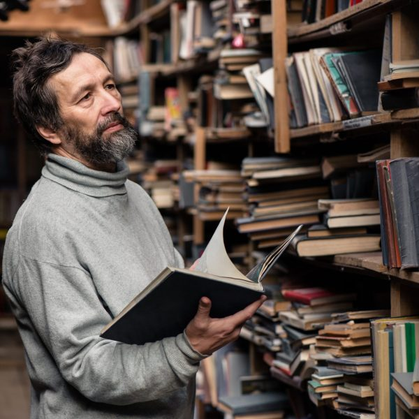 Portrait of authentic senior man with beard and good eyes reading book in the hand on  bookshelf background, The Teachings of don Juan: A Yaqui Way of Knowledge